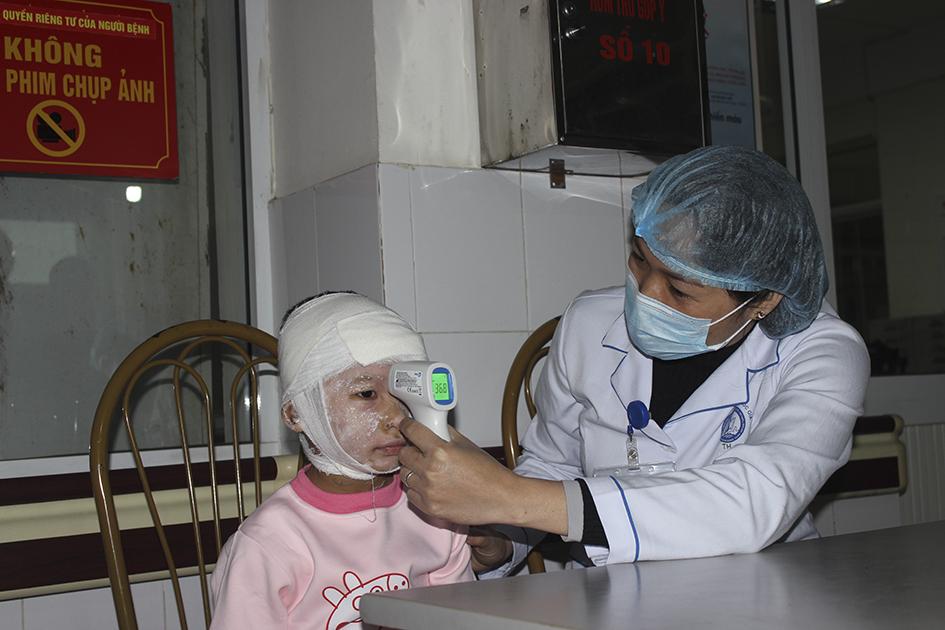 Nhân viên y tế kiểm tra lại thân nhiệt bệnh nhân bỏng trẻ em trước khi vào khoa điều trị