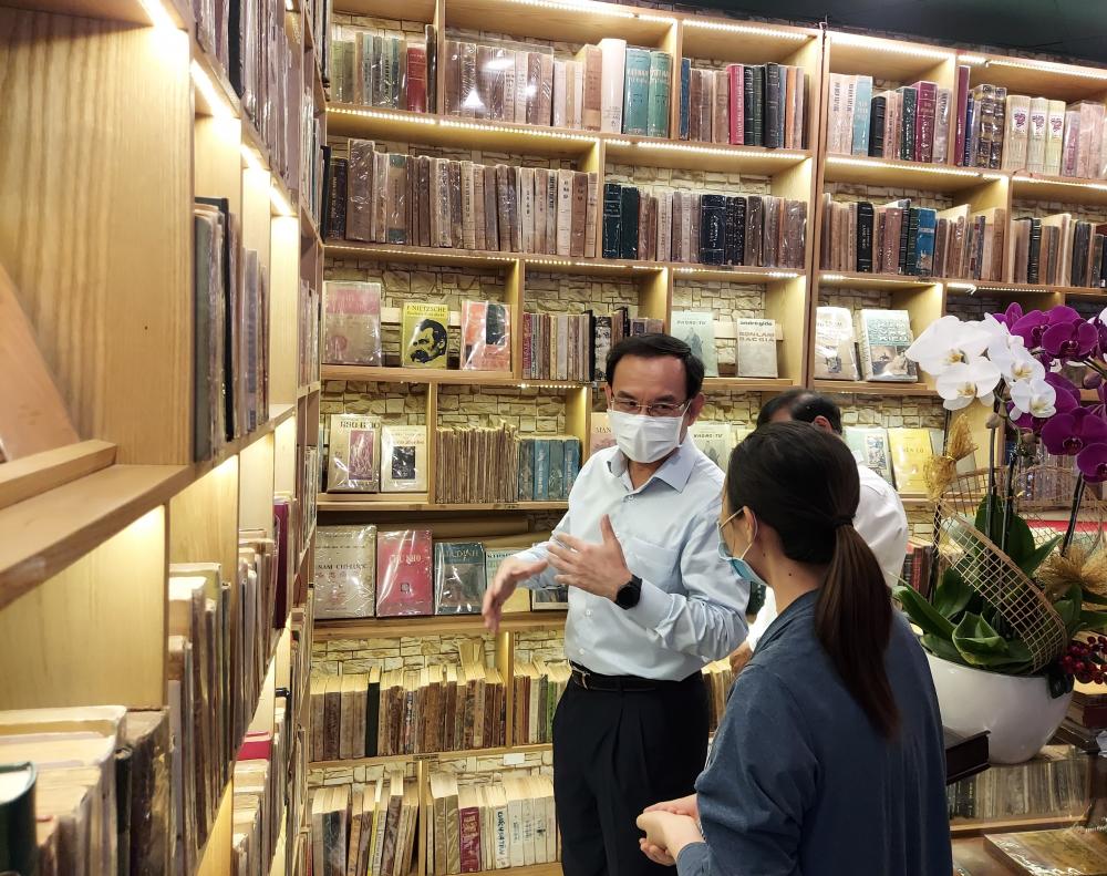 Đại diện Quán sách Mùa thu - đơn vị kinh doanh sách xưa giới thiệu các đầu sách sưu tập quý hiếm với Bí thư Thành ủy TPHCM Nguyễn Văn Nên.