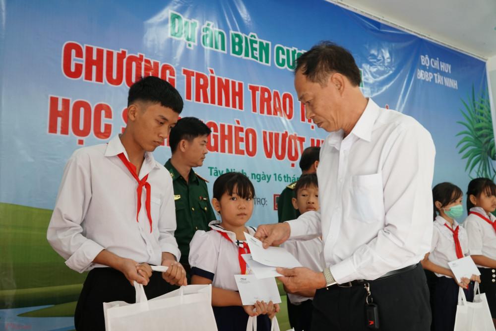 Ông Hồ Văn Đụng đại diện nhà tài trợ Agribank trao học bổng cho các em học sinh.
