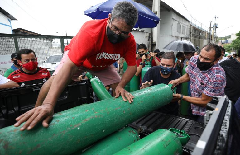 Người dân tuyệt vọng tranh cướp từng bình oxy trong khi hầu như toàn bộ hệ thống cung cấp oxy trong các bệnh viện ở thành phố Manaus đã ngưng hoạt động vì cạn kiệt nguồn cung - Ảnh: Bruno Kelly/Reuters