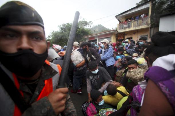 Những người lính, nhiều người đội mũ bảo hiểm, cầm khiên và gậy, xếp thành hàng ngang trên đường cao tốc ở Chiquimula, gần biên giới Honduras, để chặn đoàn người di cư.