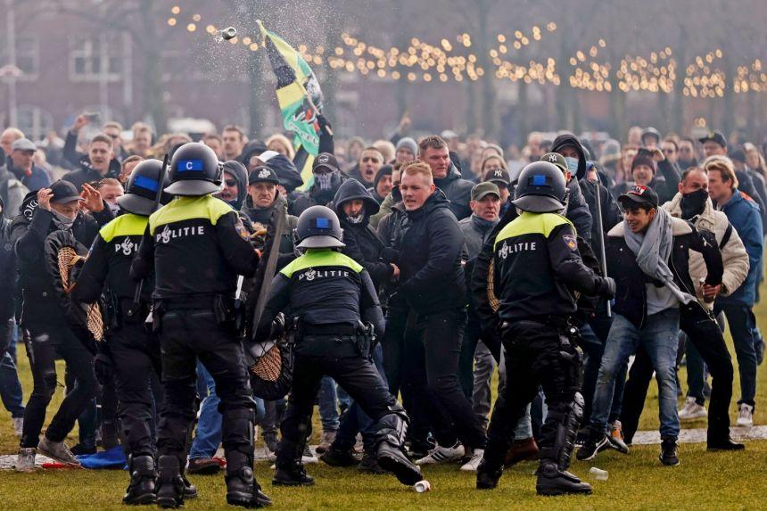 Cảnh sát chống bạo động đụng độ với người biểu tình trong cuộc biểu tình ở quảng trường thị trấn Museumplein ở Amsterdam, ngày 17 tháng 1 năm 2021