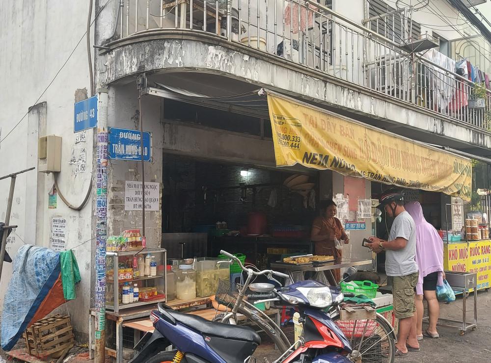 Có lẽ do tờ giấy quảng cáo dán đè lên lâu ngày nên khi xé ra bảng tên đường Trần Hưng Đạo bị tróc sơn.