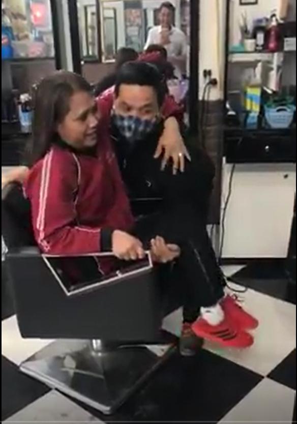 Người chồng bế vợ từ tiệm làm tóc ra xe để chở về. Ảnh cắt từ clip