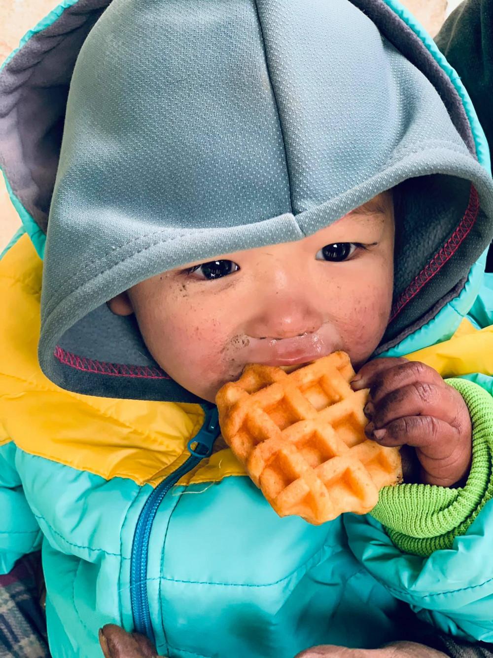 Em bé Hà Giang ăn vội miếng bánh khi mặt mũi tay chân còn lem luốc.
