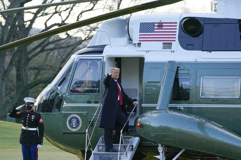 Ông Trump giơ tay chào trước khi lên máy bay
