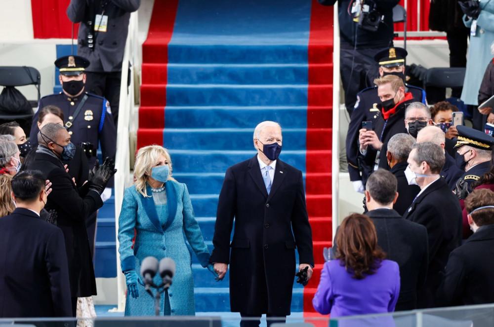 Đúng như dự đoán, Tổng thống đắc cử Joe Biden vô cùng lịch lãm khi khoác lên mình bộ vest màu xanh đậm đến từ thương hiệu Ralph Lauren. Ông không quên mang chiếc khẩu trang (đồng màu với bộ vest) cùng chiếc cà vạt xanh lam nhạt tor-sur-tor với trang phục.
