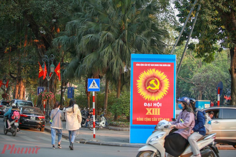 Các khu vực gần trung tâm TP. Hà Nội, vườn hoa, công viên đều rực rỡ cờ hoa. Màu chủ đạo của các tấm pano khẩu hiệu chào mừng Đại hội Đảng là vàng và đỏ.