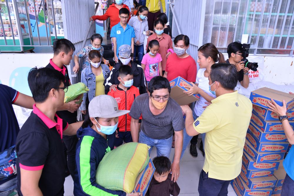 Các nghệ sỹ và tình nguyện viên gói gạo, mì trao tay các bé.