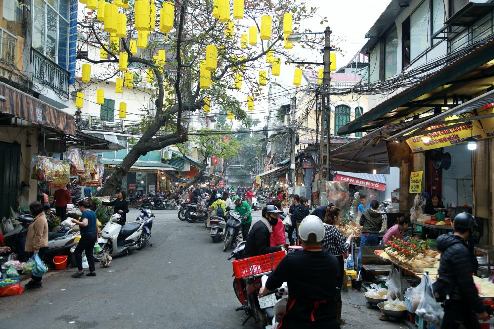 Ghi nhận của chúng tôi lại chợ Hàng Bè (Hà Nội) trong sáng 27/1 (tức Rằm tháng Chạp, Âm lịch), khu phố đã tấp nập cảnh mua bán các món đồ lễ như xôi, gà, hoa quả…