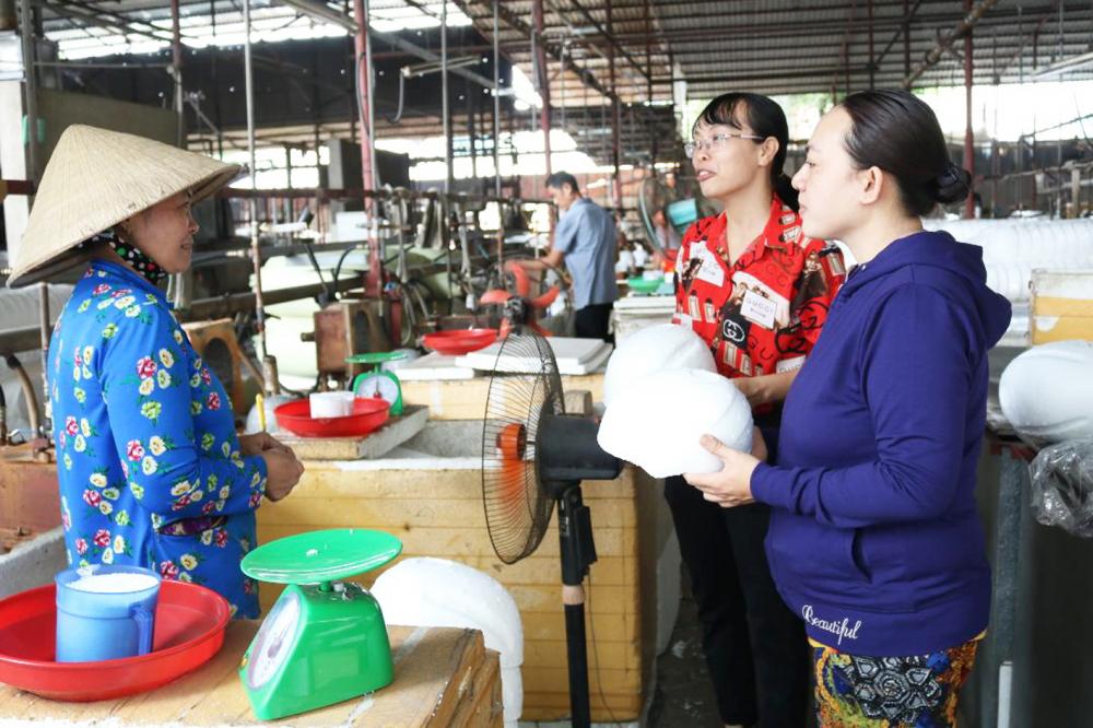 Chị Nguyễn Ngọc Trằm (bìa phải) hỏi thăm, động viên bà Gối, người đang làm việc  trong xưởng mút xốp