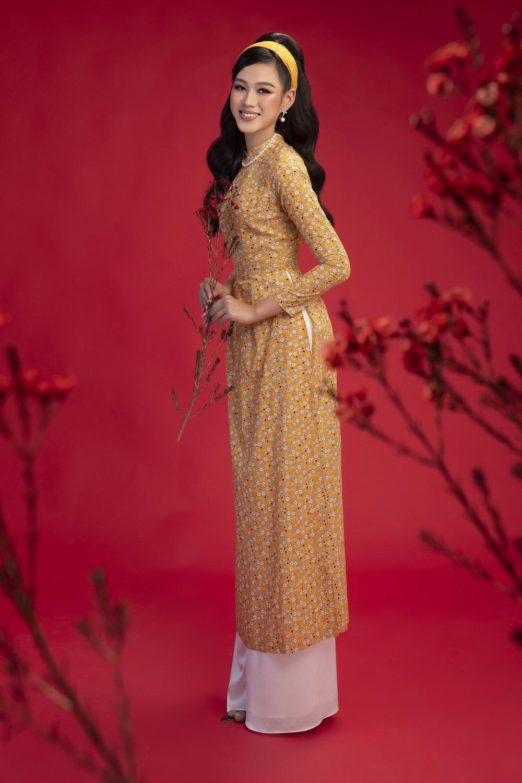 Áo dài màu vàng đất nền nã kết hợp với hoạ tiết hoa trắng