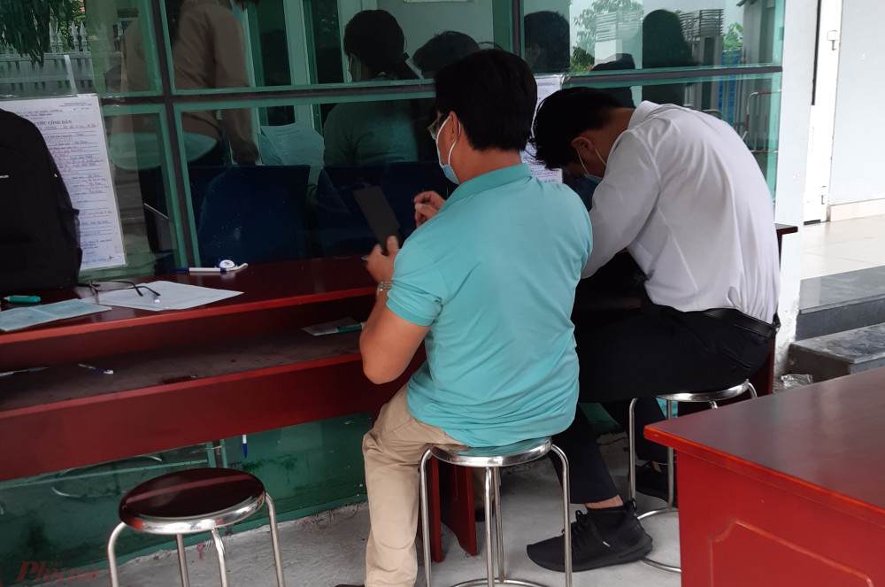 Người dân ghi tờ khai cấp căn cước công dân có gắn chip ở công an huyện Bình Chánh trước ngày 23/1 khá lo lắng vì chưa biết việc triển khai cấp mới sẽ thế nào - ảnh: Ngọc Lài.