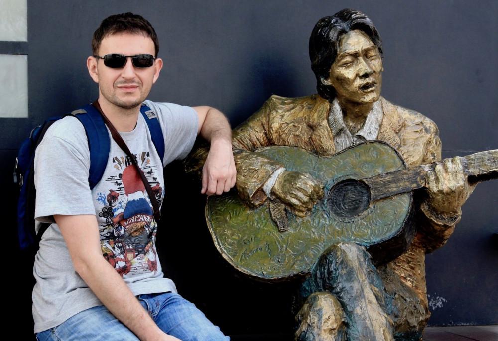 Khách du lịch bên bức tượng của cố nghệ sĩ Kim Kwang-seok.