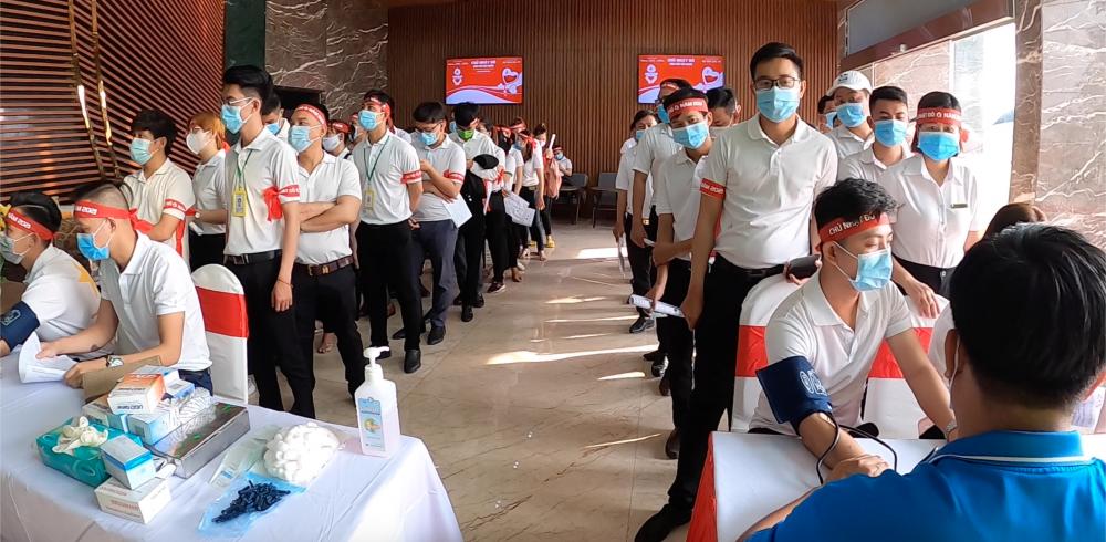 Công nhân viên chờ đến lượt để ghi thông tin, đo huyết áp