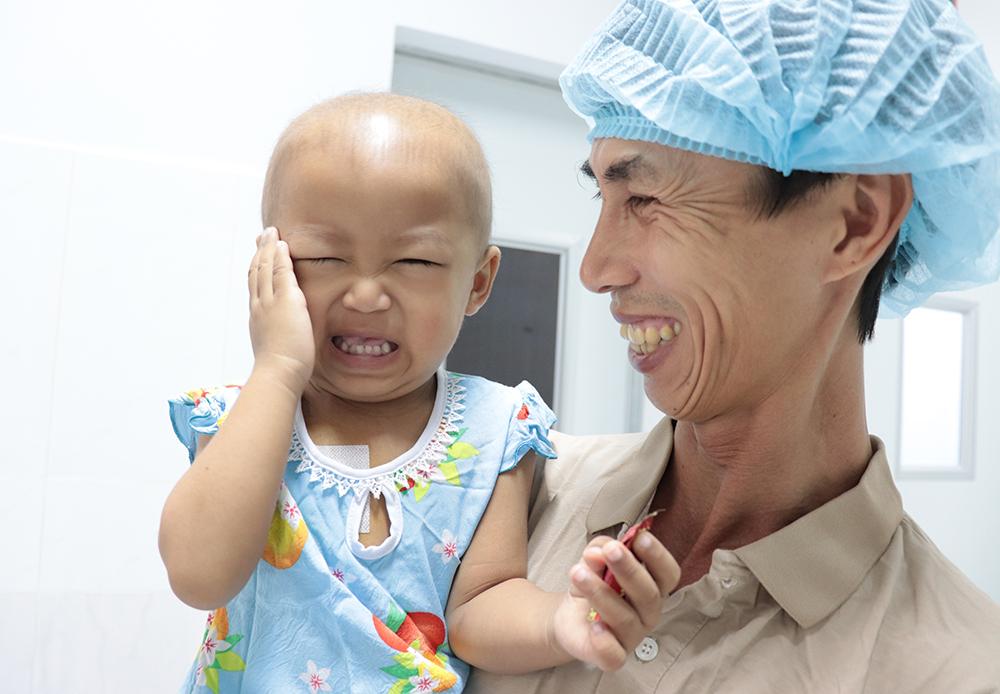 Bé Mai và cha khi nghe tin được Bệnh viện Nhi đồng 2 chữa trị, ảnh BVCC