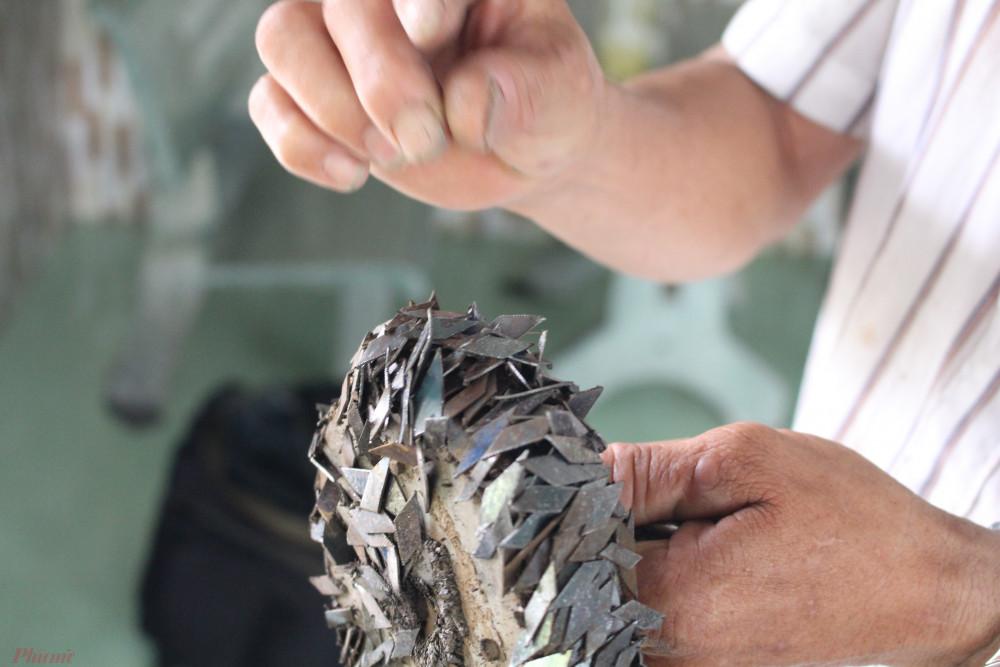 Ông Cảnh cầm dụng cụ hút đinh, đưa cho phóng viên xem những chiếc đinh sắc lẹm mà đinh tặc rải trên đường - Ảnh: Lâm Ngọc