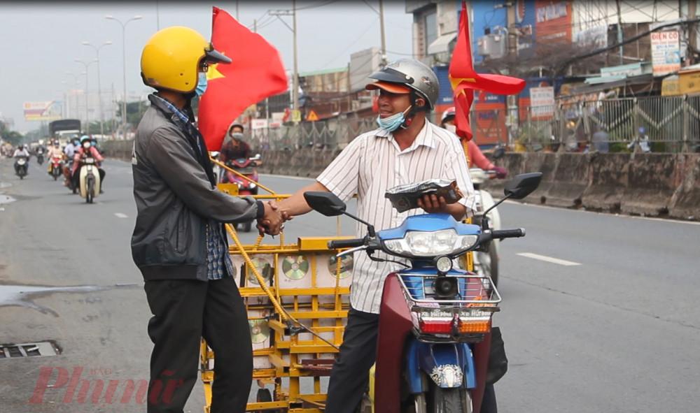 Một thanh niên chờ xe của ông Cảnh đi ngang để tặng quà - Ảnh: Lâm Ngọc