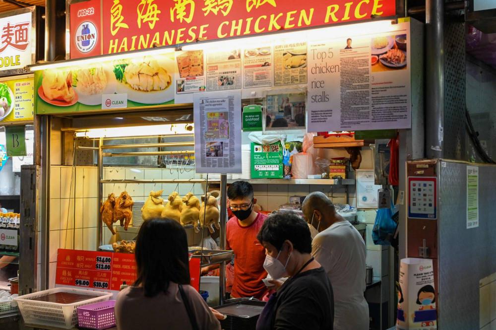 Người học việc bán hàng rong Lim Wei Keat (giữa) chuẩn bị một món ăn tại một quán cơm gà ở Singapore vào tháng Giêng - Ảnh: AFP-JIJI