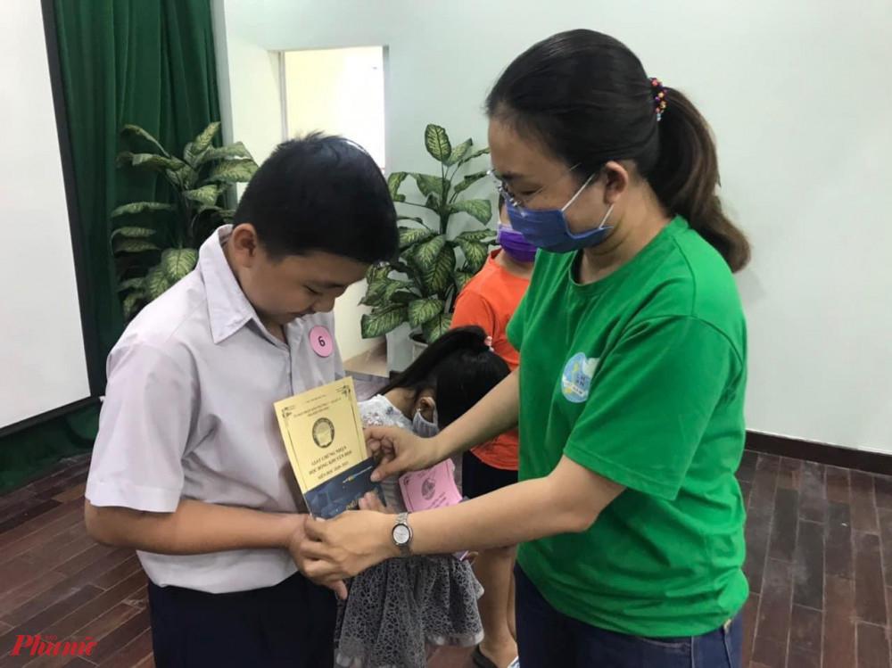 Chị Maria trích quỹ bán hàng tặng tập vở cho học sinh khó khăn.