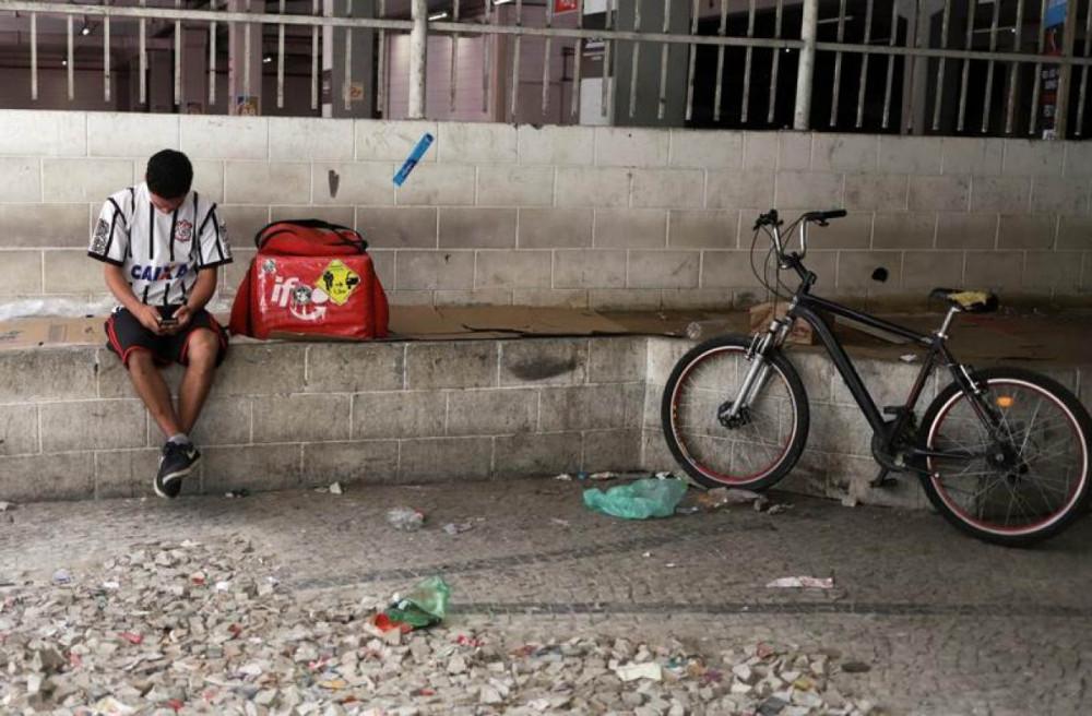 Một nhân viên giao thức ăn nhanh nghỉ chân giữa ca làm ở São Paolo. (Ảnh: Reuters)