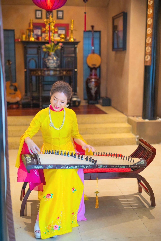 Chị Kim Dung ngồi chơi đàn trong gian nhà xưa
