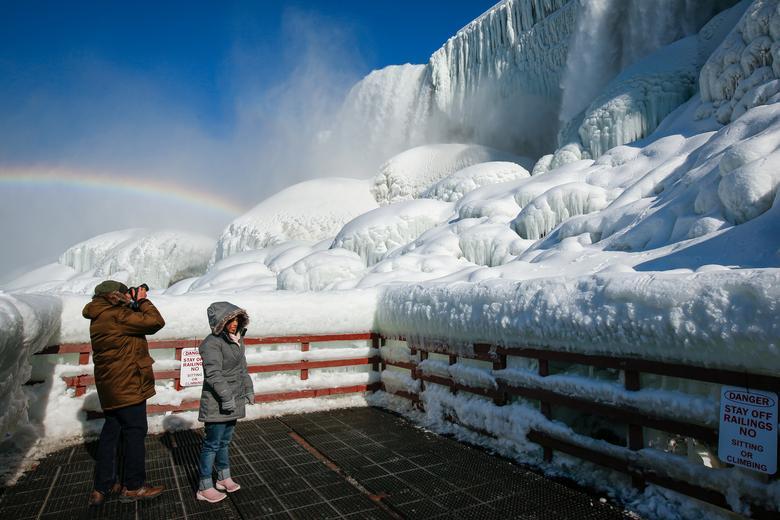 Du khách ngắm băng tuyết phủ trắng các tảng đá dưới chân thác Mỹ.