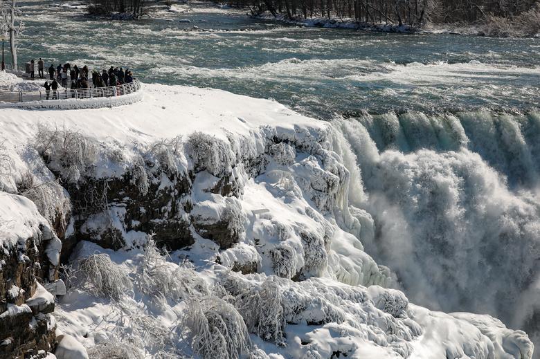 Một nhóm du khách đang ngắm nhìn dòng nước chảy siết từ thác Mỹ trong khuôn viên được rào chắn cẩn thận.