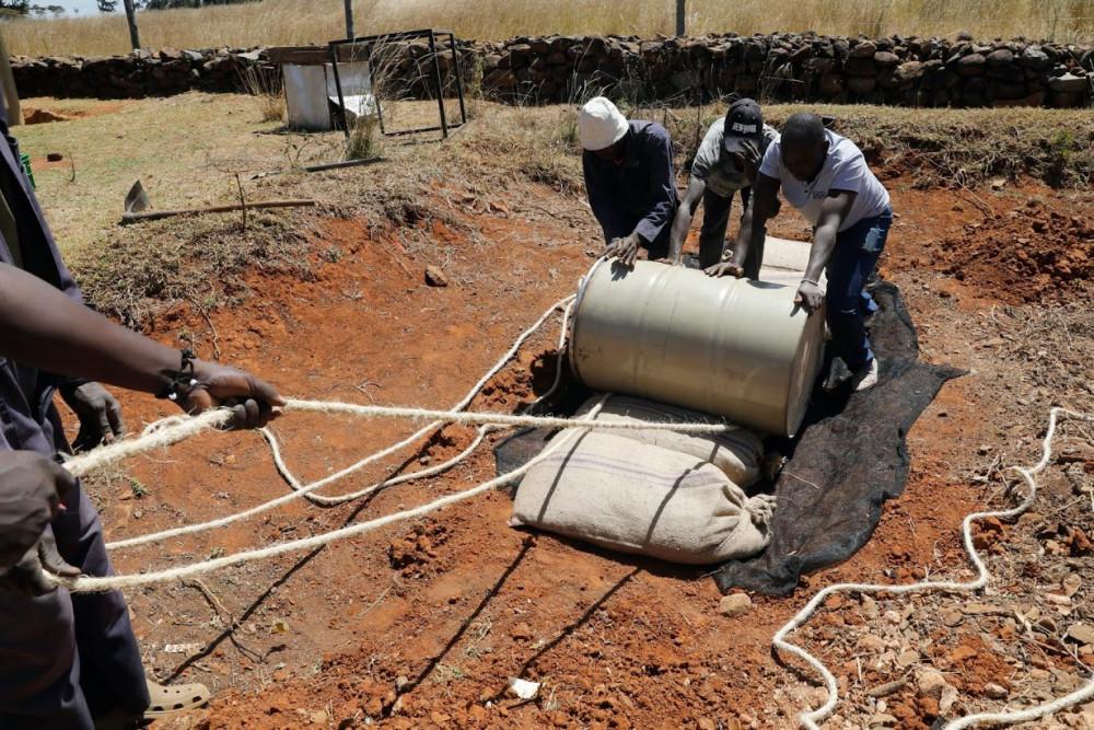 Các công nhân dùng thùng để nghiền những bao tải chứa đầy châu chấu sa mạc đã thu hoạch, tại một trang trại gần thị trấn Rumuruti.