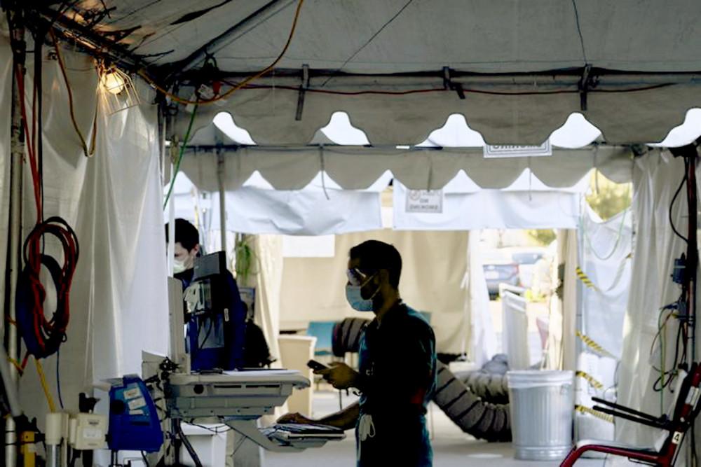Bác sĩ Nakhasi đang xem xét kết quả của bệnh nhân trên máy tính trong lều phân loại bên ngoài Bệnh viện Cộng đồng Martin Luther King Jr., Los Angeles