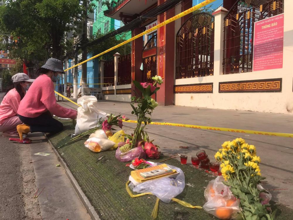 Sau khi thắp nhang, khấn vái du khách bỏ lại hoa