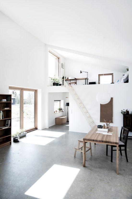Hình 7. Một ngôi nhà thoáng đãng tối giản với không gian làm việc trên gác xép có trồng cây xanh và phòng sinh hoạt chung ở dưới cầu thang tràn ngập đón nắng thông qua cửa sổ áp mái.