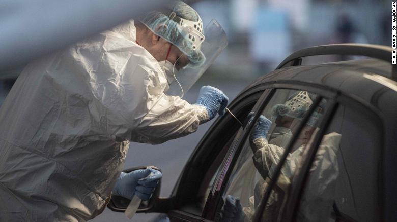 Nhân viên y tế lấy mẫu tại trạm xét nghiệm COVID-19 dành cho người lái xe ở Praha