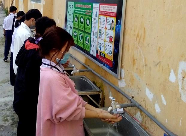 Học sinh ở Đồng Tháp đeo khẩu trang và rửa tay trước khi vào lơp học nhằm phòng chống COVID-19