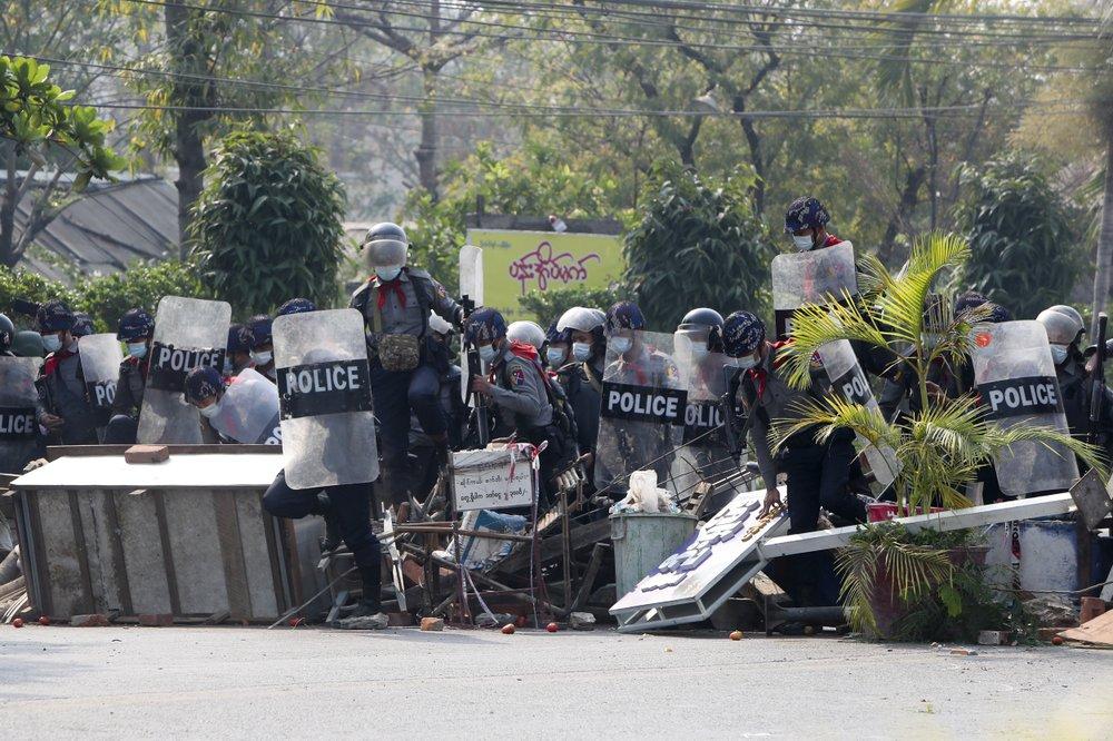 Cảnh sát chống bạo động Myanmar với lá chắn vượt qua hàng rào do người biểu tình dựng lên trong cuộc biểu tình phản đối cuộc đảo chính quân sự ở Mandalay.