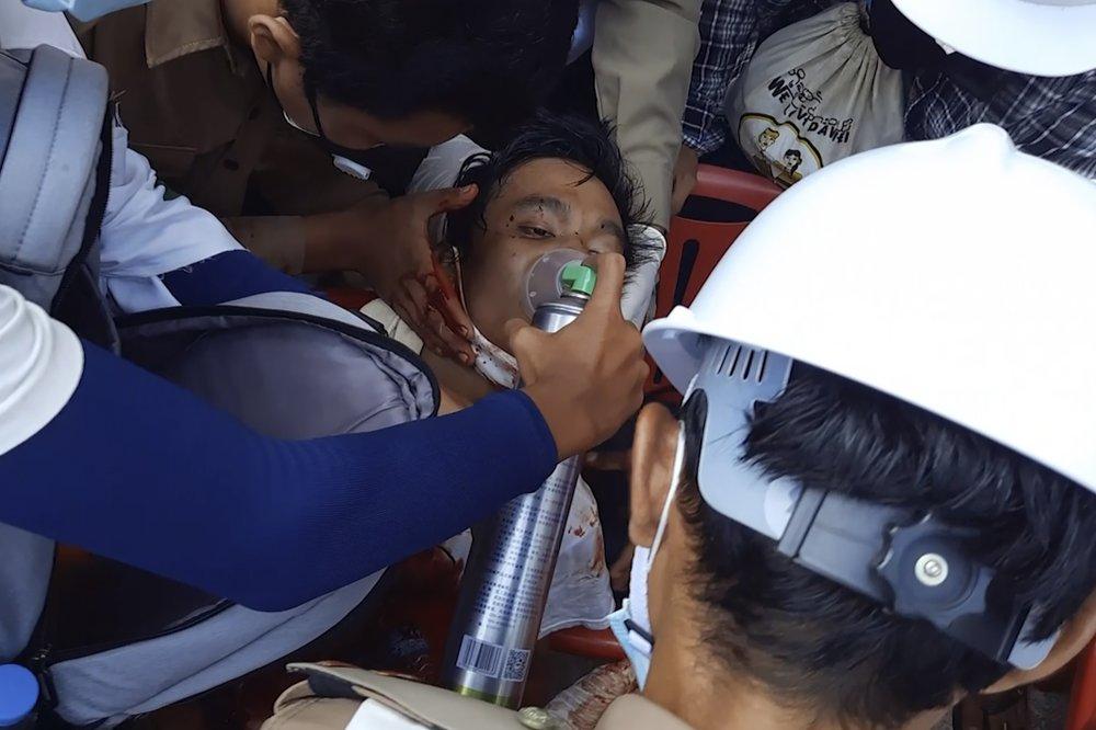 Các bác sĩ chăm sóc một người đàn ông trên một con phố ở Dawei, Myanmar.