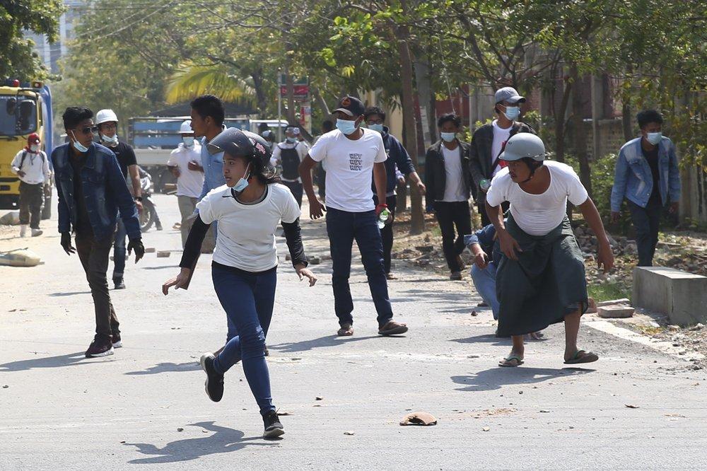 Người biểu tình chạy khi cảnh sát bắn hơi cay trong cuộc biểu tình phản đối cuộc đảo chính quân sự ở Mandalay.