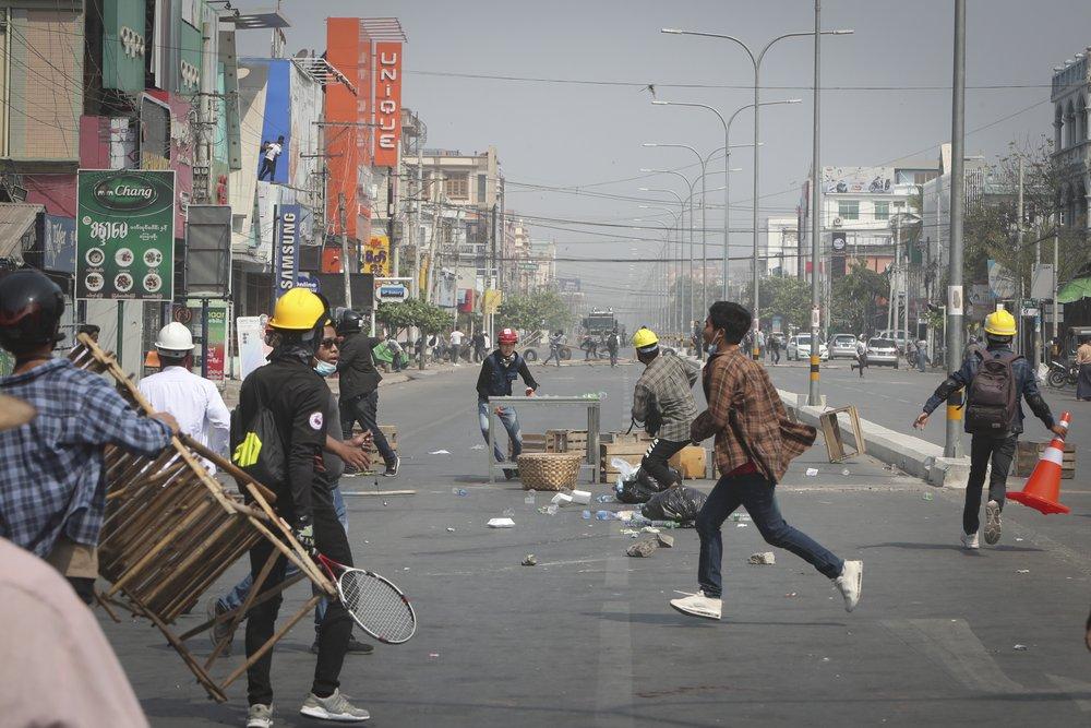 Người biểu tình cố gắng chặn đường khi cảnh sát đến trong cuộc biểu tình phản đối cuộc đảo chính quân sự ở Mandalay, Myanmar.