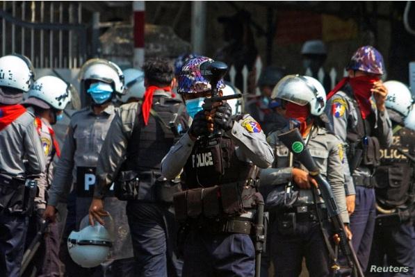 Một sĩ quan cảnh sát chống bạo động bắn đạn cao su về phía người biểu tình trong cuộc tuần hành phản đối đảo chính quân sự ở Yangon, Myanmar hôm 28/2