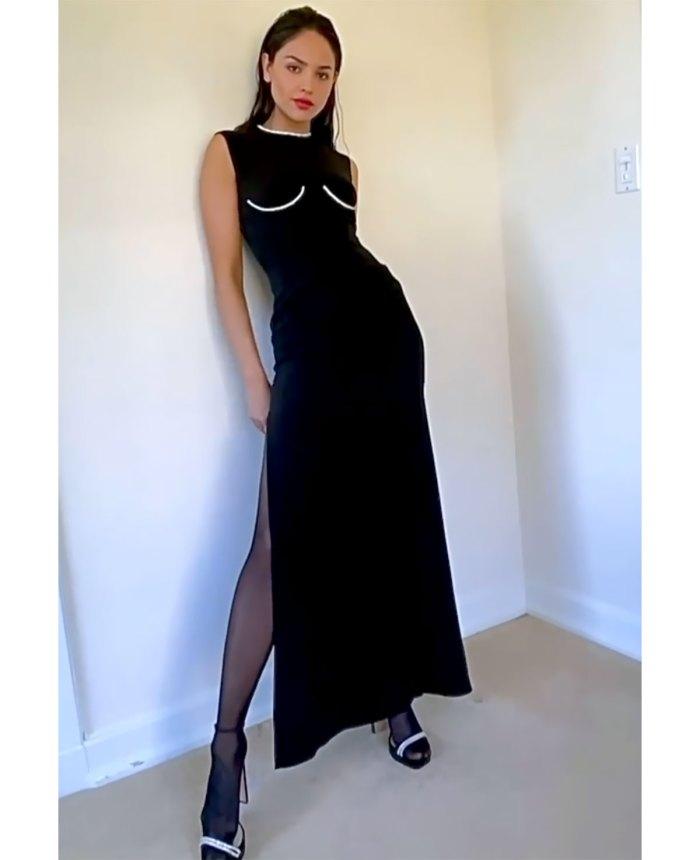 Eiza Gonzalez gợi cảm trong mẫu váy đen Versace xẻ tà cao. Đường viền cổ áo và vạt áo màu bạc giúp tranh phục tránh sự đơn điệu.