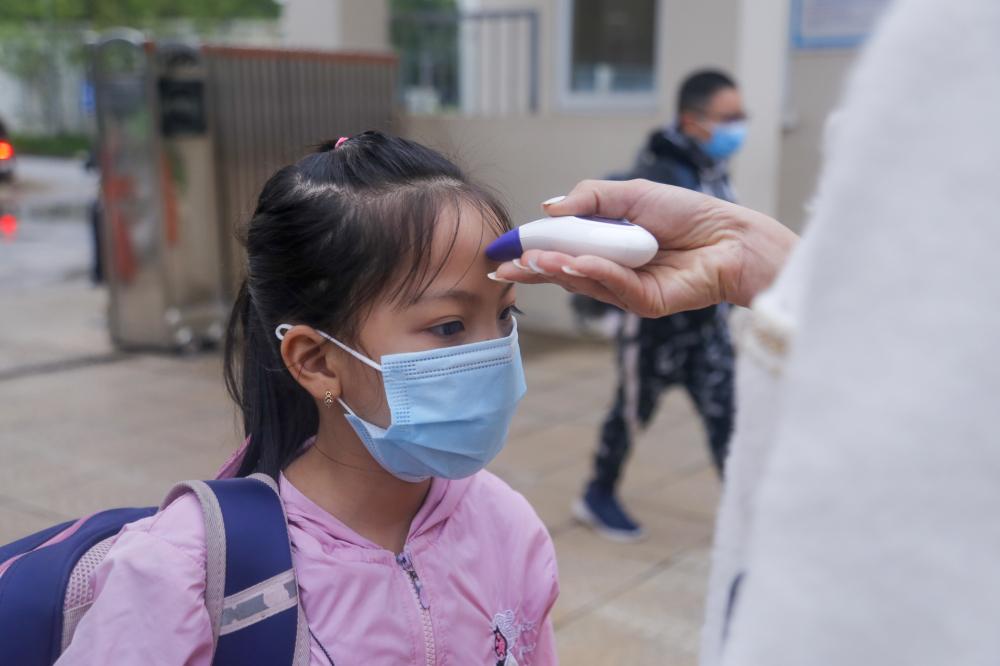 Học sinh được các cô giáo đo thân nhiệt trước khi vào cổng trường