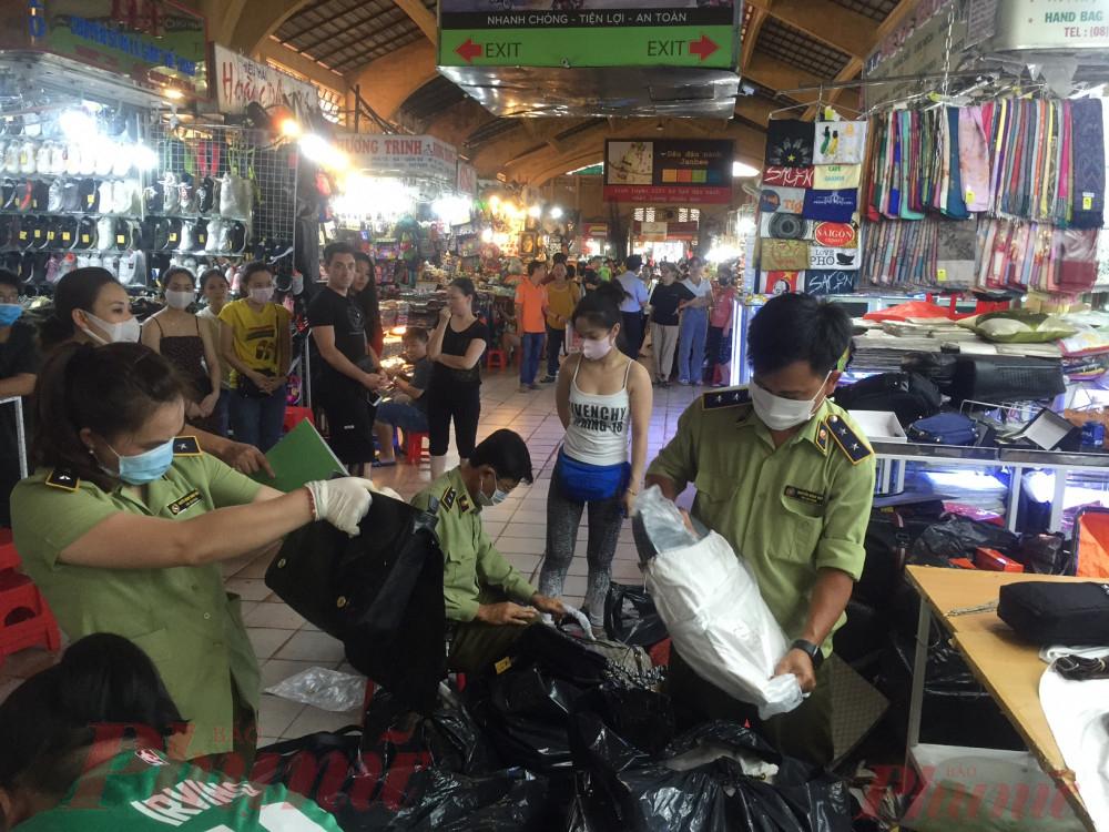 Lực lượng quản lý thị trường kiểm tra, thu giữ hàng giả tại chợ Bến Thành, TP.HCM.