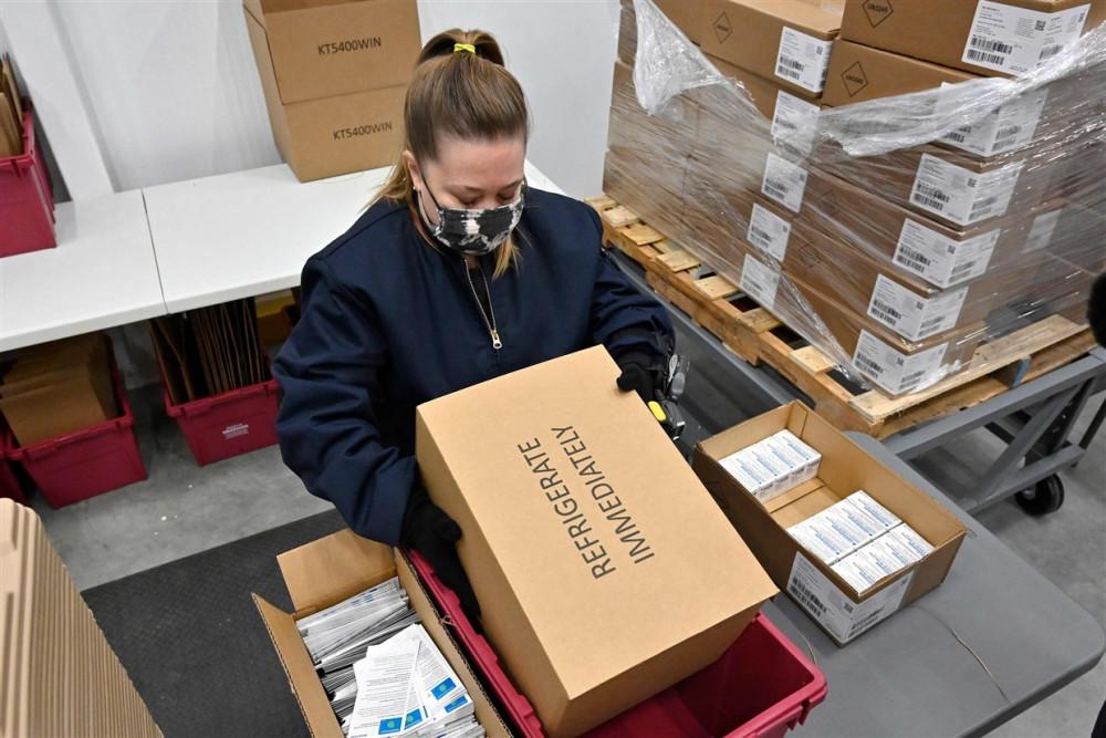 Một nhân viên của McKesson Corporation đặt vắc-xin COVID-19 Johnson & Johnson vào một thùng vận chuyển ở Shepherdsville - Ảnh: AFP