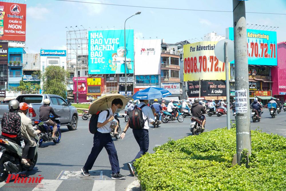 Quá nắng, nhiều học sinh phải dùng dù che nắng khi di chuyển trên đường