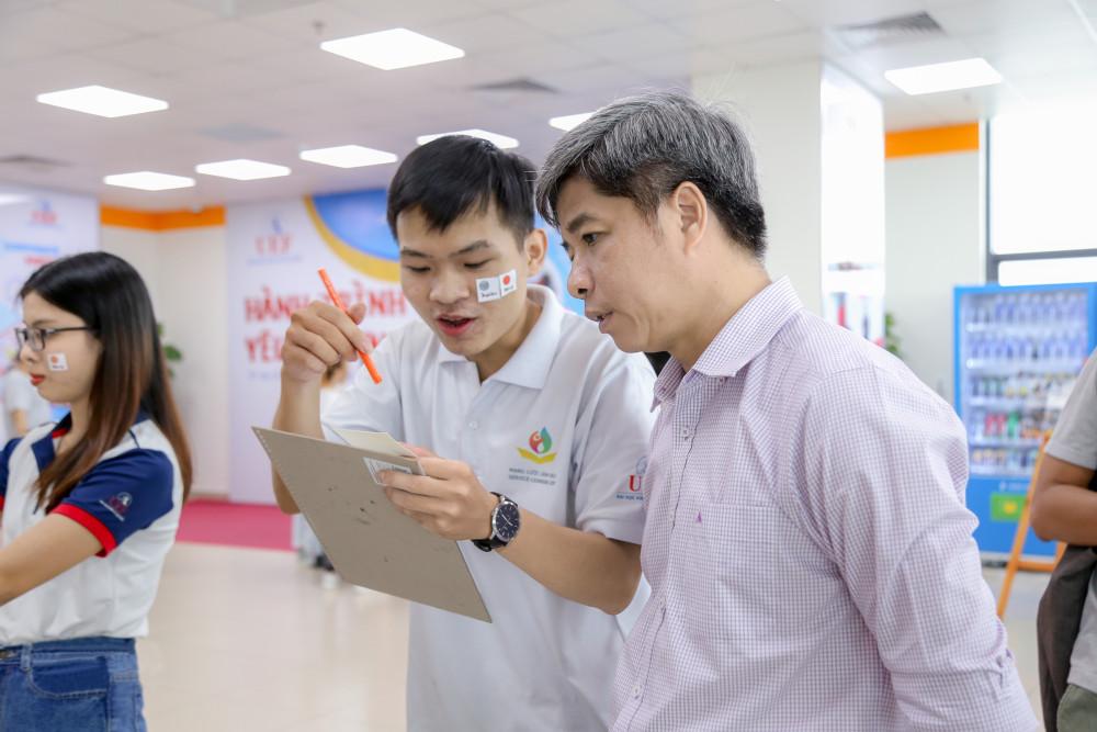 Tiến sĩ Nguyễn Thanh Giang, Hiệu trưởng Trường đại học Kinh tế - Tài chính TP.HCM (phải), trao đổi cùng sinh viên - ảnh: trương bích