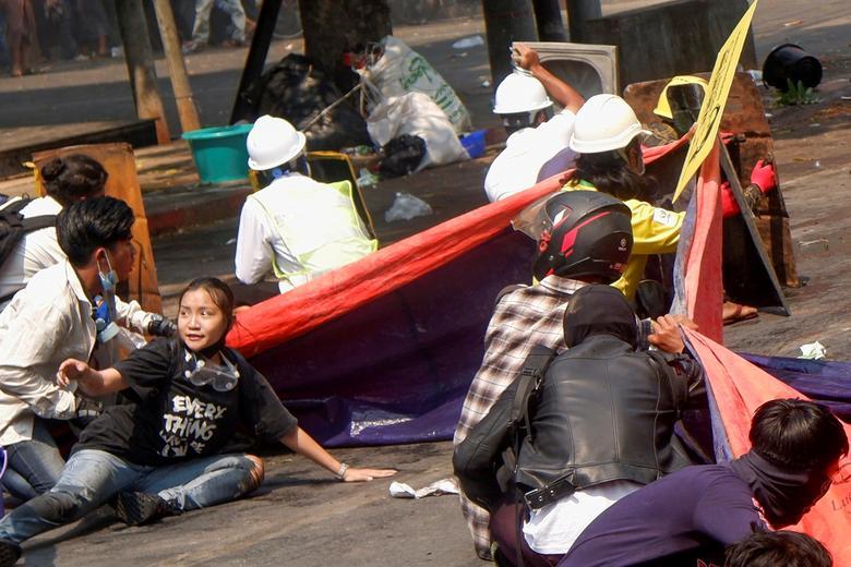 Angel (góc dưới bên trái) né tránh cùng những người biểu tình khác sau khi cảnh sát nổ súng để giải tán một cuộc biểu tình chống đảo chính ở Mandalay, Myanmar, ngày 3/3/2021. Chiếc áo của cô gái 19 tuổi ghi dòng chữ Mọi thứ sẽ ổn, dù cô ấy biết rõ rằng mọi thứ có thể không ổn. Angel, tên thật là Kyal Sin, đã bị giết bởi một phát đạn vào đầu trên đường phố Mandalay khi đấu tranh cho nền dân chủ mà trong đó cô đã tự hào bỏ phiếu lần đầu tiên vào năm ngoái, một cuộc bầu cử bị quân đội đảo chính cáo buộc lvô căn cứ à gian dối