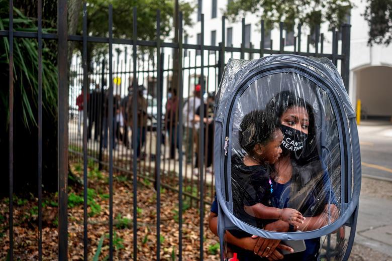 Dana Clark và con trai 18 tháng tuổi Mason xếp hàng chờ đợi tại Tòa thị chính khi cuộc bỏ phiếu sớm bắt đầu cho cuộc bầu cử tổng thống Mỹ năm 2020 ở New Orleans, Louisiana, ngày 16/10/2020