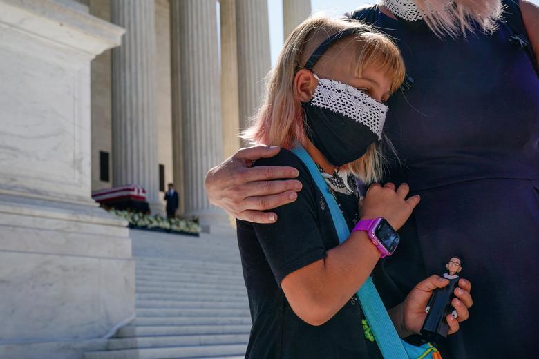 Neva Gotwals-Ferrei (8 tuổi) ôm mẹ cùng búp bê mang hình ảnh bà thẩm phán Ruth Bader Ginsburg. Bà  Ginsburg lúc ấy đang nằm yên nghỉ tại Tòa án tối cao Mỹ ở Washington, ngày 23/9/2020
