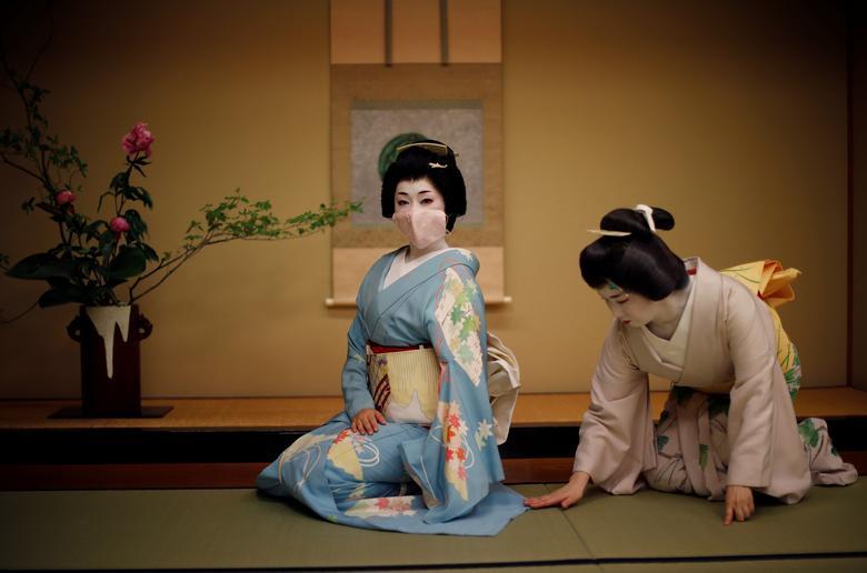 Mayu chỉnh trang kimono cho Koiku, khi Koiku bận tạo dáng chụp ảnh. Hai geisha chuẩn bị biểu diễn tại một bữa tiệc ở nhà hàng sang trọng giữa phố thị Tokyo, Nhật Bản