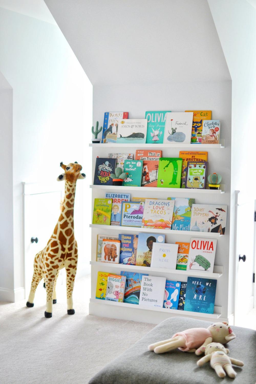 Hình 9. Một không gian thoải mái để đọc sách được trang trí kệ sách với những cuốn sách trẻ em đầy màu sắc cùng một chiếc ghế êm ái và những người bạn nhỏ xinh xắn.